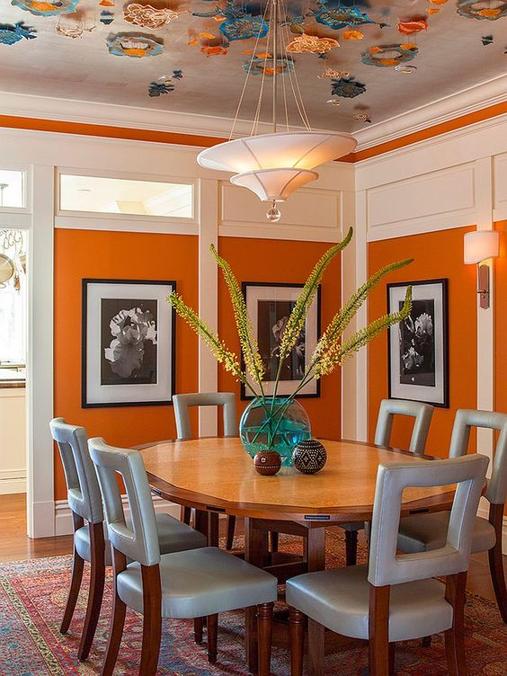 beautiful modern dining room with orange wall and grey chairs luxazin